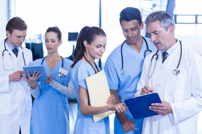 Medical team discussing paperwork on clipboard. At the hospital stock image