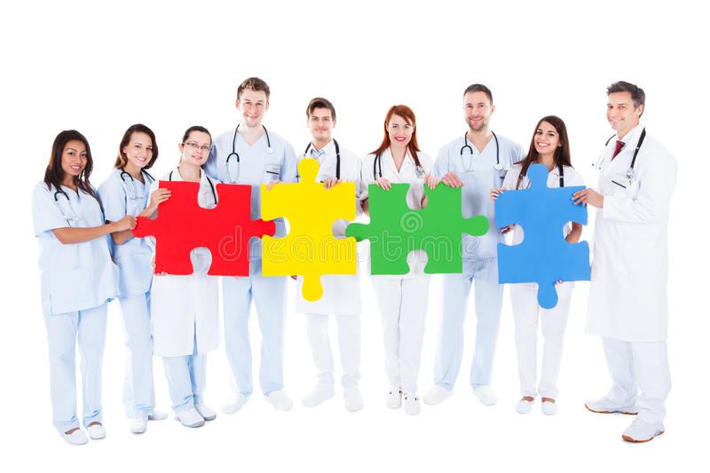 Medical team holding colorful puzzle pieces royalty free stock image