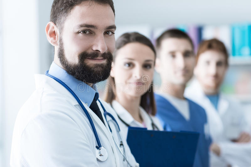 Medical team at the hospital. Medical team posing at the hospital they are standing and looking at camera, healthcare and teamwork concept stock photography
