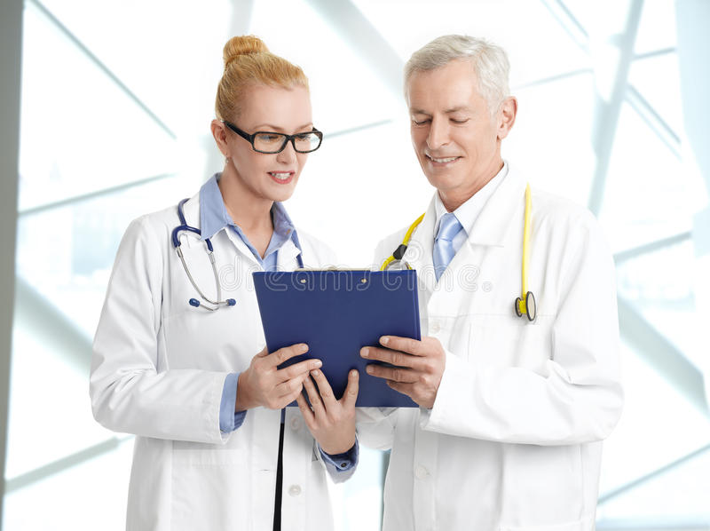 Medical team. Image of medical team consulting. Portrait of female doctor holding clipboard and consulting with senior doctor while standing at private clinic stock photo