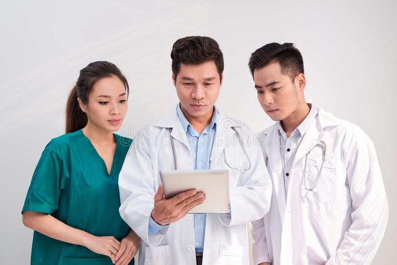Medical team includes doctors and nurse looking at an ipad/tablet computer together.  royalty free stock photo