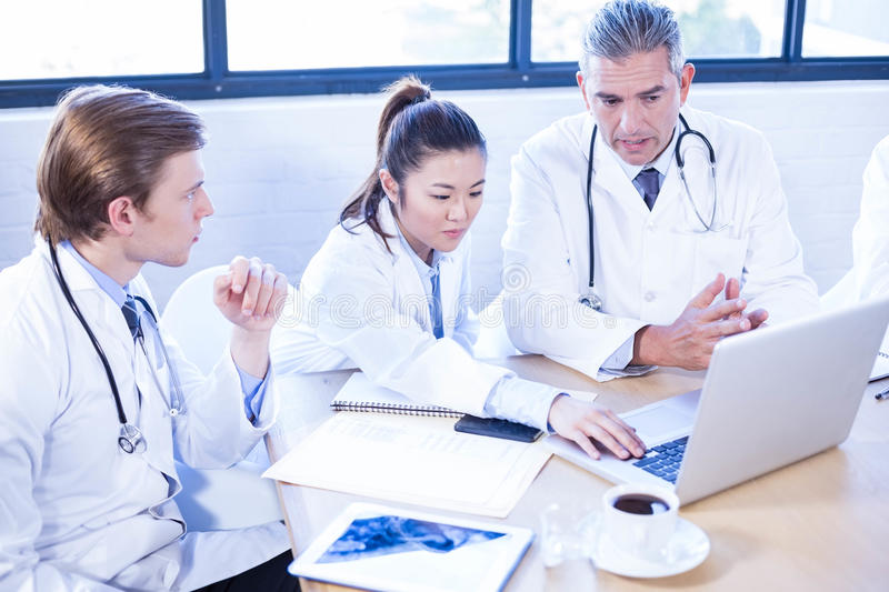 Medical team looking into laptop and having a discussion. At conference room stock photos