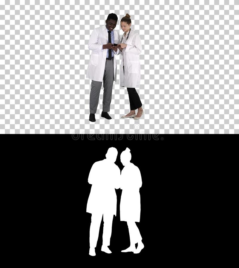 Medical team looking at phone together, Alpha Channel royalty free stock photography