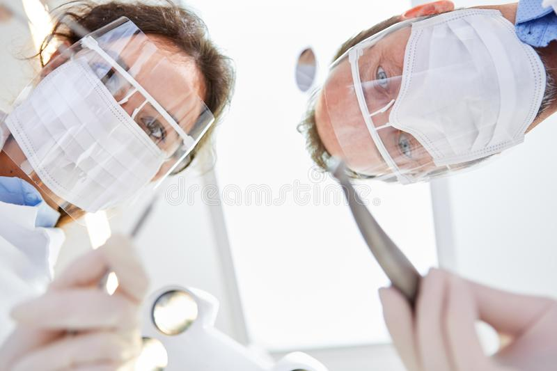 Medical team with mask and visor before surgery. Dentists as a medical team with surgical mask and visor before surgery in the dental clinic stock image