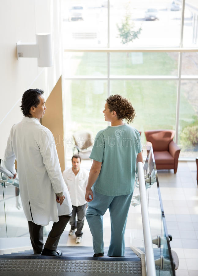 Medical Team And Patient Walking On Stairs stock photos