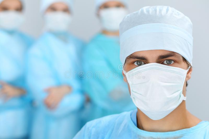 Medical team performing operation. Focus at male doctor.  royalty free stock photo