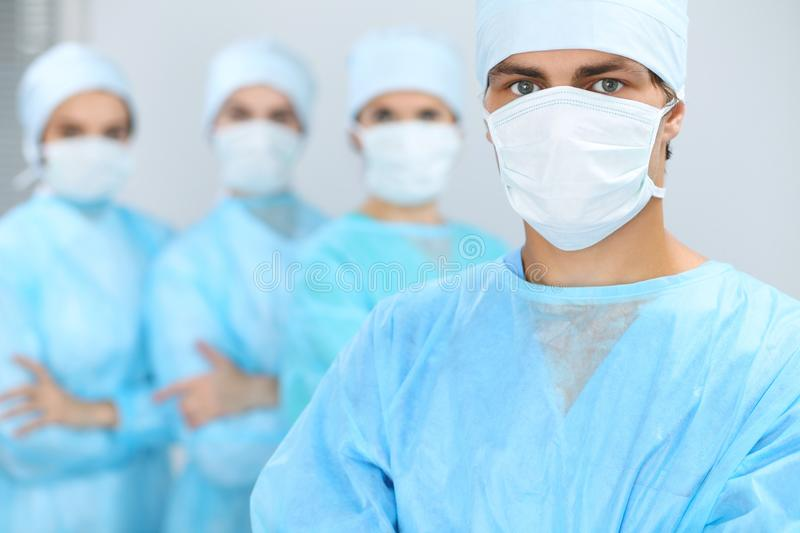 Medical team performing operation. Focus at male doctor.  royalty free stock image