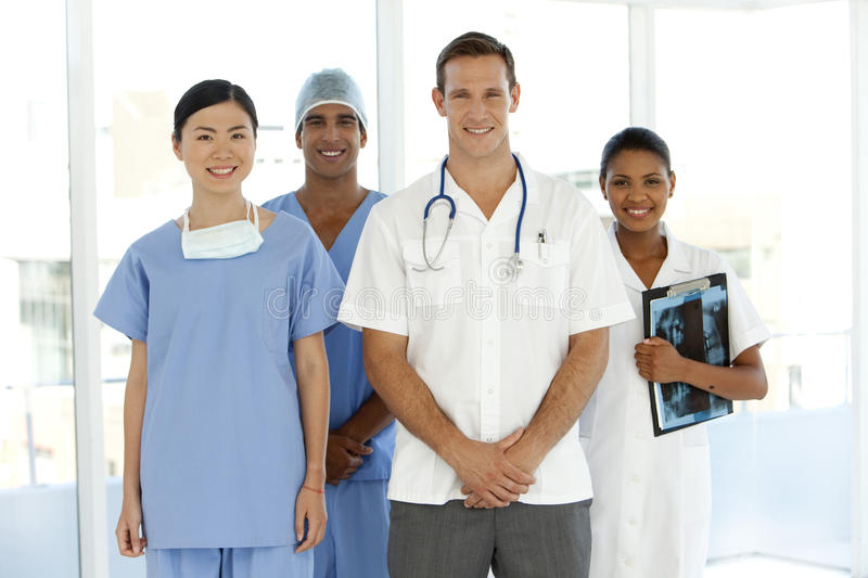 Medical team. Portrait of a multi-ethnic medical team including Caucasian, Asian, Afro-American and Indian members. They stand in a row with white men as leader royalty free stock photo