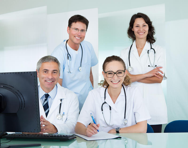 Medical team posing in an office. Medical team comprising male and female doctors posing together in an office smiling at the camera stock photos