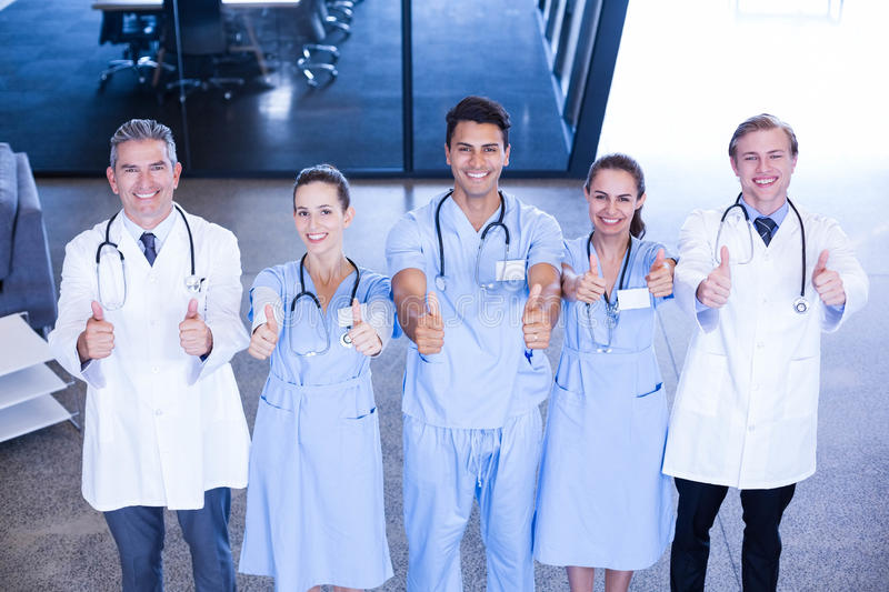 Medical team putting their thumbs up and smiling stock photography