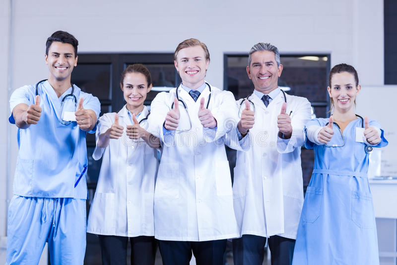 Medical team putting their thumbs up and smiling. Portrait of medical team putting their thumbs up and smiling in hospital royalty free stock image
