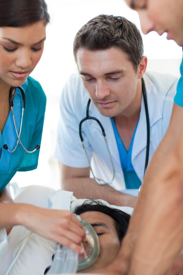 Medical team resuscitating a patient. Multi-ethic medical team resuscitating a patient. Medical concept stock photos