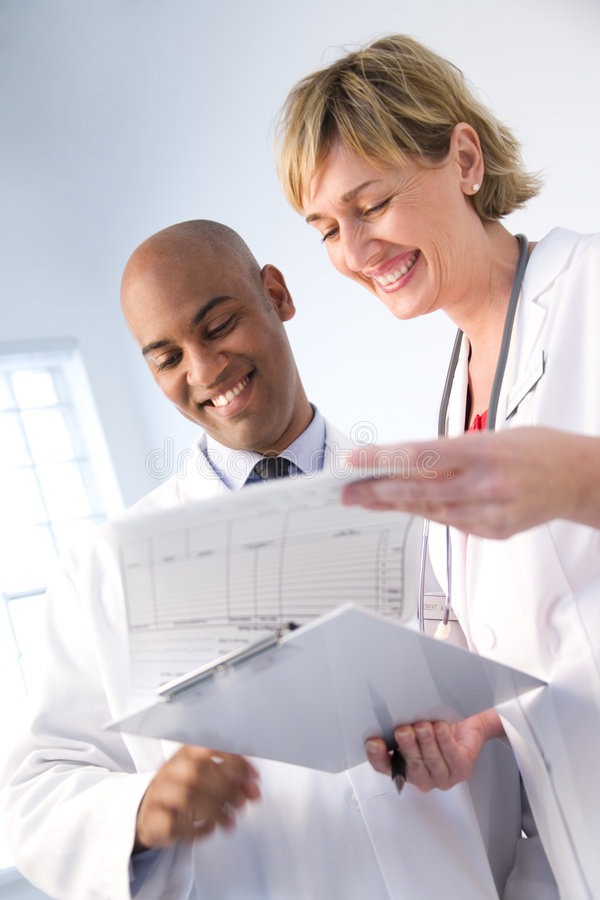 Medical team reviewing chart. A view of medical technicians or doctors reviewing a patient's chart