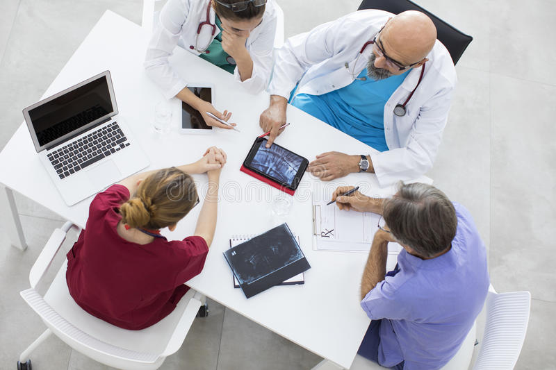 Medical team sitting and discussing at table. Medical team sitting and discussing at the table stock image