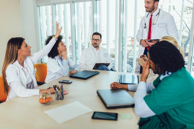 Medical team sitting and discussing at the table royalty free stock photography