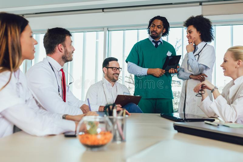 Medical team sitting and discussing at the table stock photos