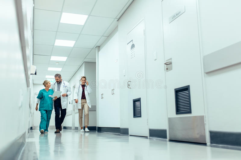 Medical team walking down hallway at the hospital royalty free stock photo