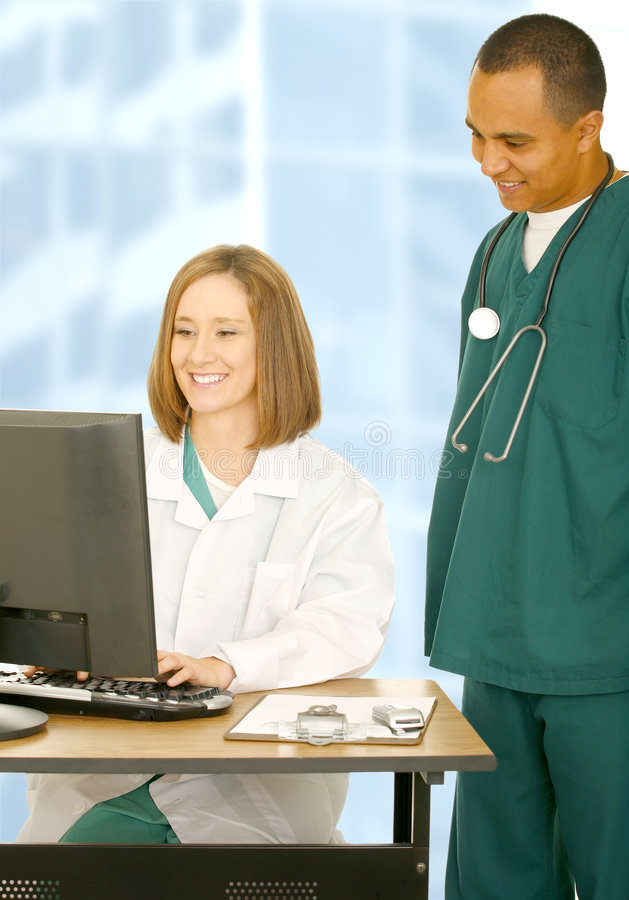Medical Team Working On Computer. Two medical team working. the woman typing on computer and the man is looking at the screen royalty free stock image