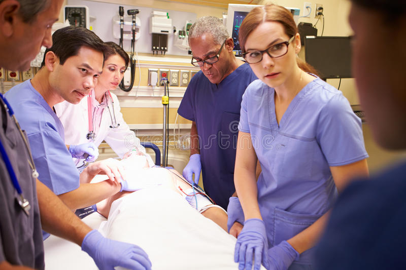 Medical Team Working On Patient In Emergency Room. Looking At Doctor stock images
