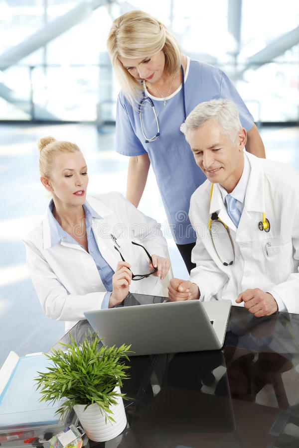 Medical team. Working togehter on laptop at clinic stock images