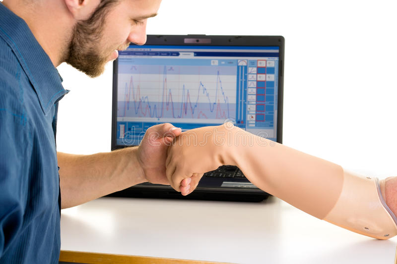 Medical technician looks over prosthetic arm. Computer-controlled adjusting. stock photos
