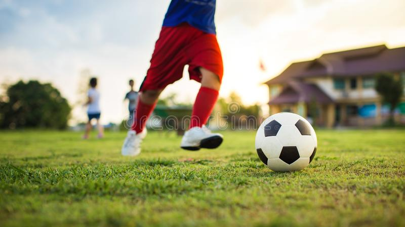 Action sport outdoors of a group of kids having fun playing soccer football for exercise in community rural area under the twiligh royalty free stock images