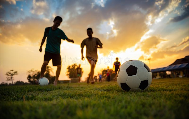 Silhouette action sport outdoors of a group of kids having fun playing soccer football for exercise in community rural area under. Medical technologist working stock photos