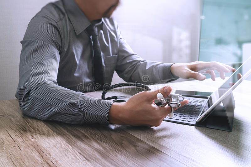 Medical technology concept. Doctor hand working with modern digital tablet dock screen computer with medical chart interface, Sun. Flare effect photo stock image