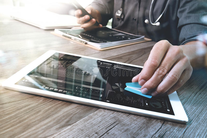 Medical technology concept. Doctor hand working with modern digital tablet and laptop computer with medical chart interface, Sun. Flare effect photo royalty free stock photos