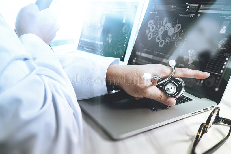 Medical technology concept. Doctor hand working with modern digital tablet and laptop computer with medical chart interface, Sun. Flare effect photo stock photo