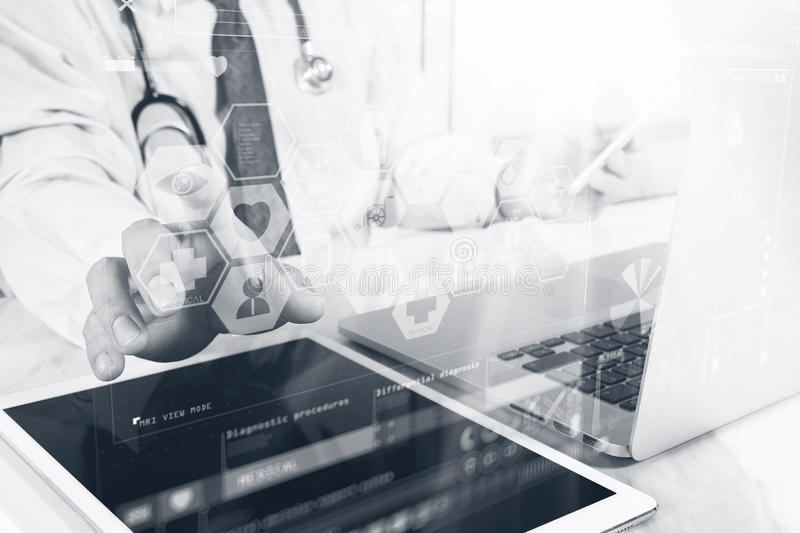 Medical technology concept. Doctor hand working with modern digital tablet and laptop computer with medical chart interface, Sun. Flare effect photo, black royalty free stock photo