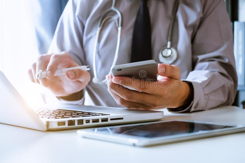 Medical technology concept. Doctor working with mobile phone and stethoscope in modern office. Medical technology concept. Doctor working with mobile phone and stock photography