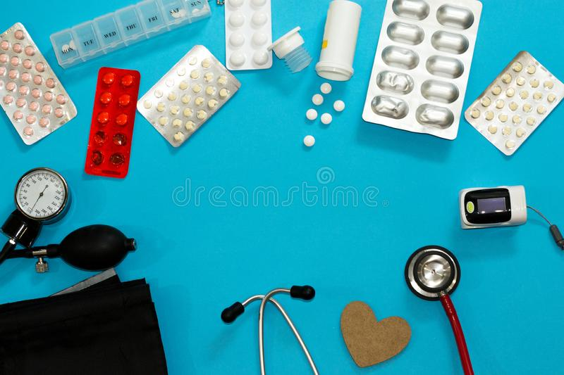 Medical tools and pills blisters for theat and diagnose patients on blue background with copy space. Stethoscope, cuff, pulse stock images