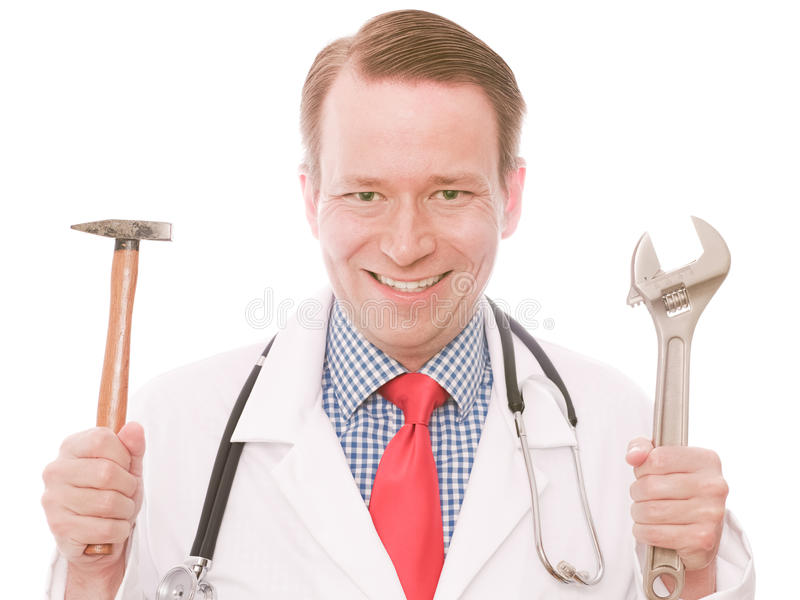 Medical tools. Young happy smiling physician holding a hammer and a wrench as a funny concept for medical instruments - isolated on white and retouched royalty free stock photography
