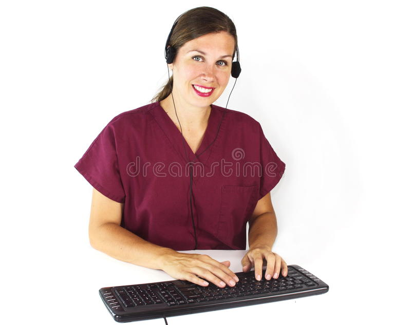 Medical Transcription. Smiling nurse with brown hair doing medical transcription work. Using a keyboard and headset royalty free stock image