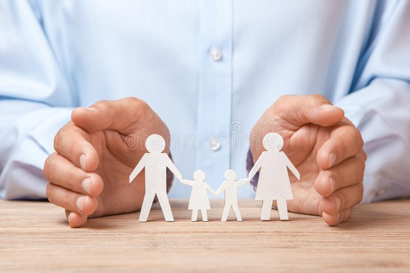 Medical or travel insurance. Man covers the family with his hands from his father, mother, son and daughter royalty free stock images