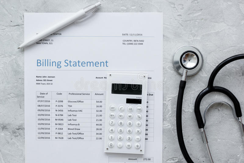 Medical treatmant billing statement with stethoscope and calculator on stone background top view stock image