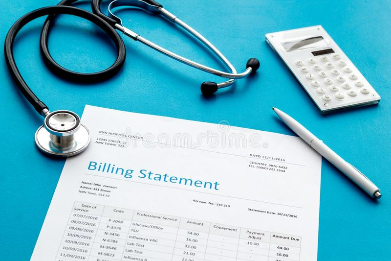 Medical treatment bill, calculator and phonendoscope on blue background. Medical treatment bill, calculator and phonendoscope on blue desk background royalty free stock photo