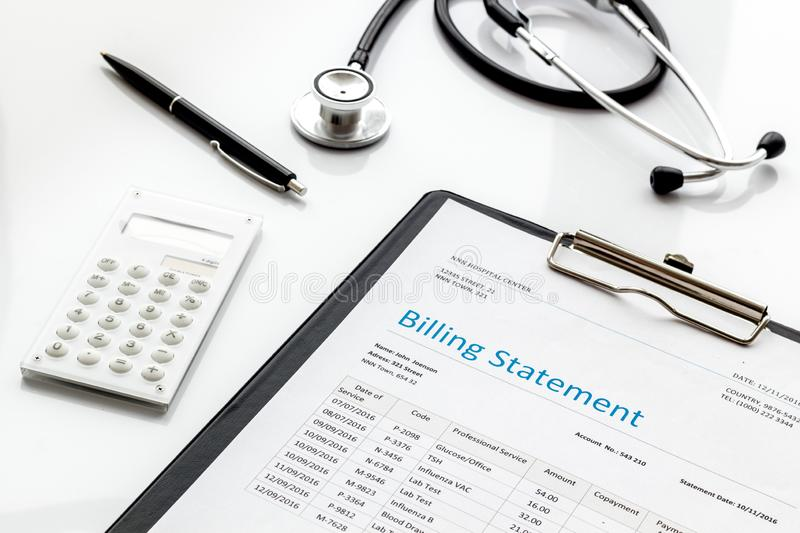 Medical treatment bill, calculator and phonendoscope on white background. Medical treatment bill, calculator and phonendoscope on white desk background royalty free stock image