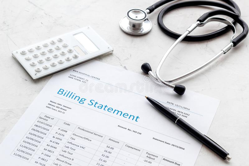 Medical treatment bill, calculator and phonendoscope on white background. Medical treatment bill, calculator and phonendoscope on white desk background stock image