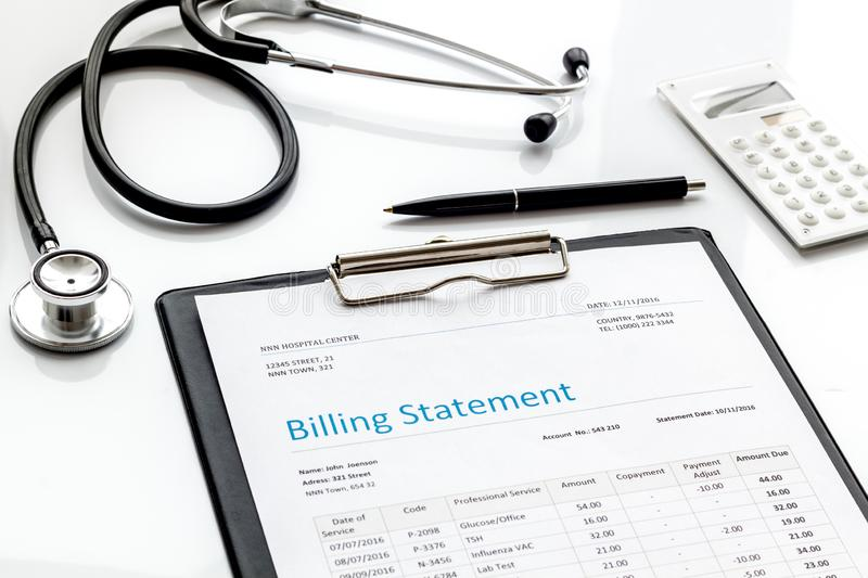 Medical treatment bill, calculator and phonendoscope on white background. Medical treatment bill, calculator and phonendoscope on white desk background royalty free stock photo