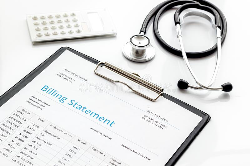 Medical treatment bill, calculator and phonendoscope on white background. Medical treatment bill, calculator and phonendoscope on white desk background stock photography