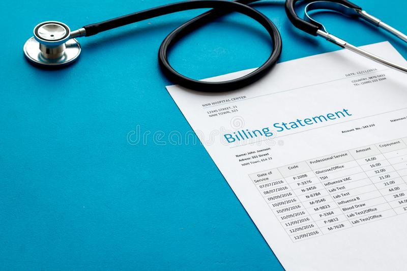 Medical treatment bill and phonendoscope on blue background royalty free stock photo