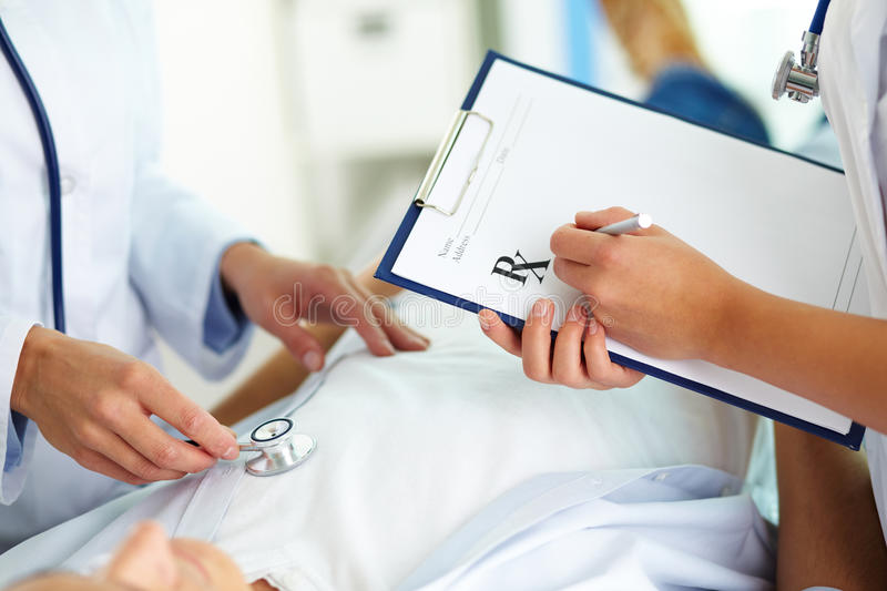 Medical treatment. Close-up of female doctors hands during medical treatment of patient in hospital stock image