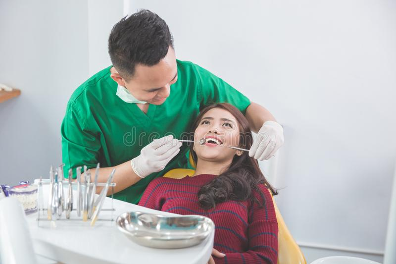 Medical treatment at the dentist office. Male dentist Medical treatment to a female patient at the clinic royalty free stock image