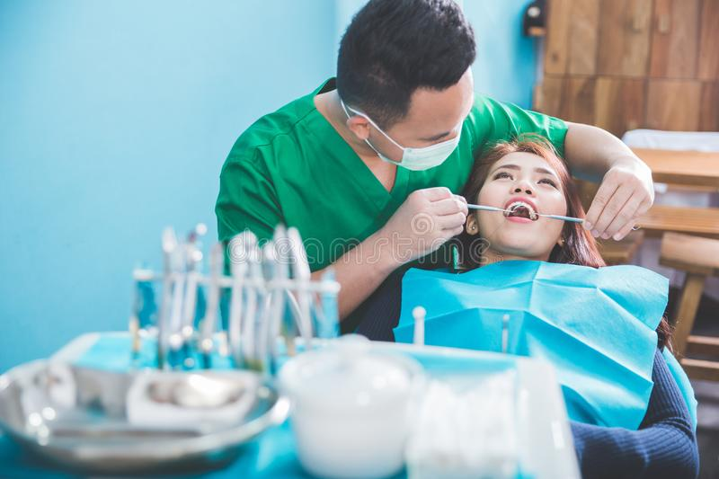 Medical treatment at the dentist office. Male dentist Medical treatment to a female patient at the clinic stock photography