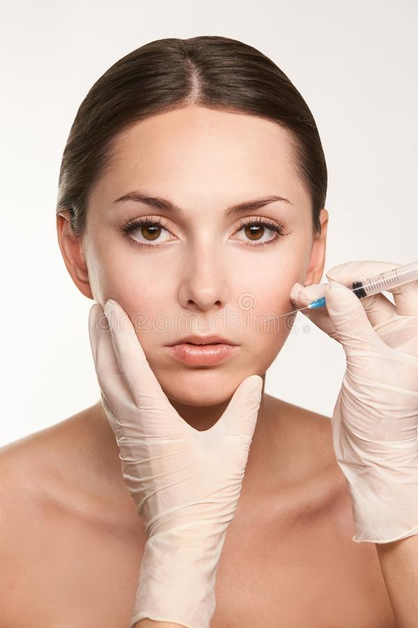 Medical treatment. doctor injecting anto wrinkle. cosmetology procedure for young girl.  royalty free stock photography