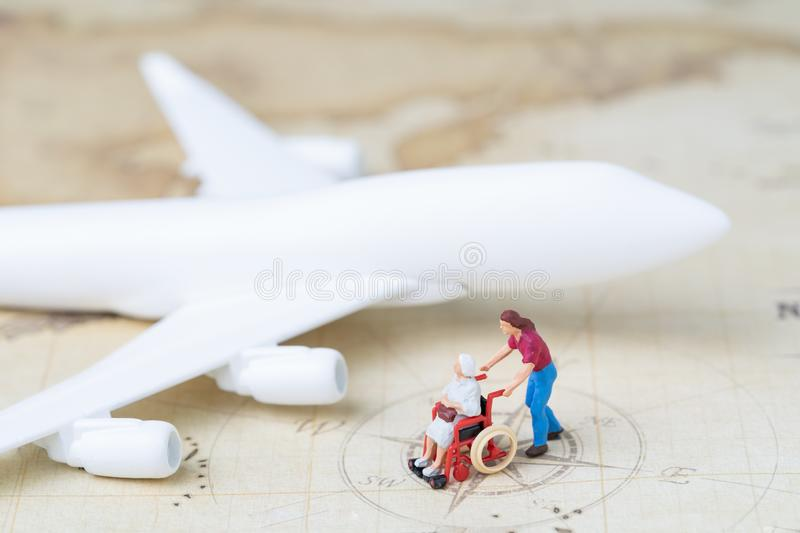 Medical trip planning or travel concept, miniature senior elderly people on wheelchair with son or caregiver standing with toy ai royalty free stock images