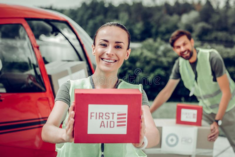 Medical worker holding first aid box sending humanitarian help. First aid box. Dark-eyed medical worker holding red first aid box while sending humanitarian help stock image