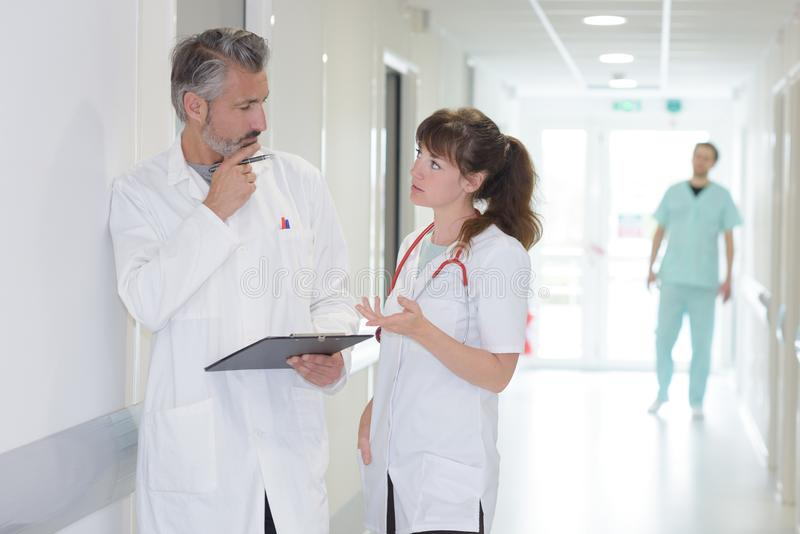 Medical workers in discussion in hospital corridor stock photo
